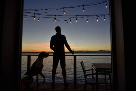 Man and dog silhouetted on seaside deck at sunset under hanging deck lights. RLTheis