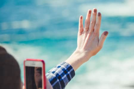Young woman takes photos of engagement ring after getting engaged by the ocean.
