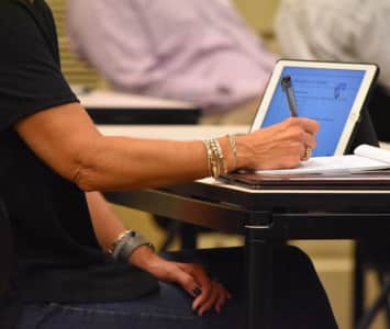 Woman Taking notes at a business conference while working on a laptop