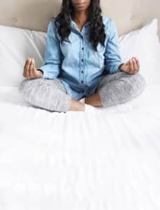 African American woman sitting crossed legged on bed wearing a slight smile of peace as she does a morning mediation routine to bring calm and focus to her day