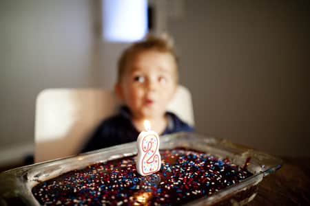 toddler boy blowing out his candles on a chocolate cake with at number 1 candle lit