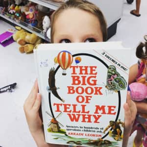 boy holds up a book that is called the big book of tell me why in front of his face