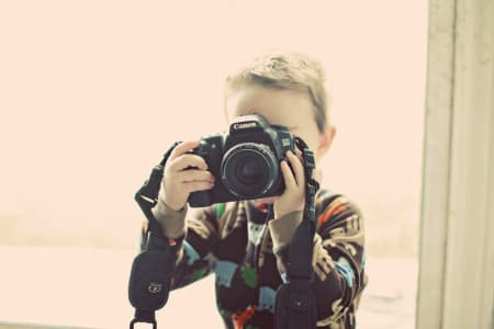 little boy holding an SLR camera and taking a photo