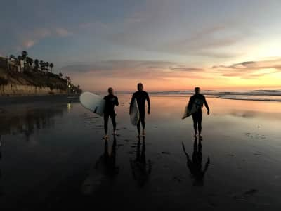 Surfers leaving the beach at sunset after surfing .