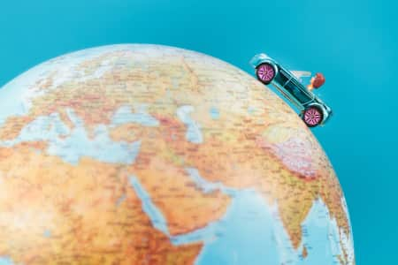 Concept of travelling around the world. Car toy going around globe toy