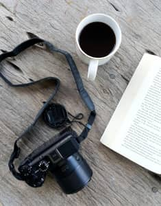 Top view of black camera with hot black coffee cup and open pocket book in woode table background