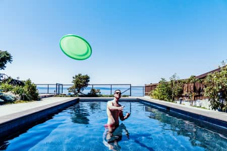 Man standing in beautiful backyard swimming pool throwing green frisbee disc against blue sky. RLTheis
