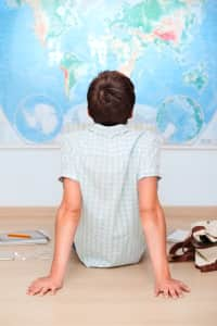 Boy sitting on the floor in front of the map of the world in the classroom at school. Back to school