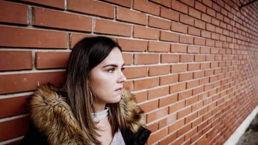 Urban portrait of a young woman in front of a brick wall. Young millenial in a winter jacket.