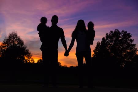 A Beautiful couple with small children is holding hands on sunset standing together as a family holding hands (Nominated)