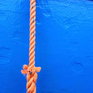 Orange rope dangling in front of a blue hull.