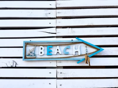 Arrow beach sign on a white wooden wall