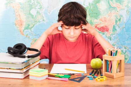 Boy doing a homework resolving difficult math problem. Student sitting at desk. World map in the background. Back to school