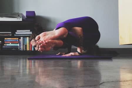 Woman doing Yoga in purple leggings with kitty in the background