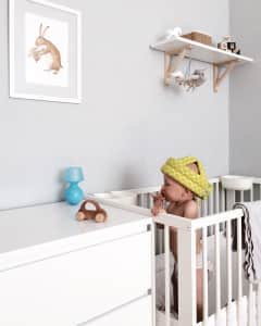 Baby with a protective helmet, nursery, wooden toy car