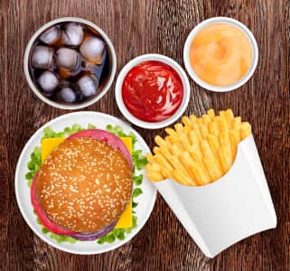 Fast food. Sandwich and fries, sauces and cold drink. Food and drink on a table