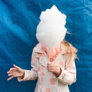 Girl holding big candy floss in the front of face standing over blue background. Sweet food