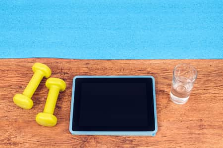 Ready for workout. Workout with video course. Using technology to fitness training. Dumbbells, tablet and gym mat