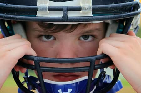 Closeup of young athlete with hands on his football helmet and determination in his eyes.