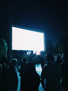 Outdoor screen at night for a cinema cession with people watching in a dark blue atmosphere