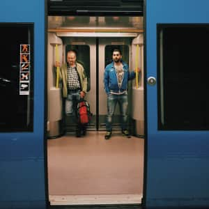 Passengers / travelers in subway, blue doors, two men standing, urban life and lifestyle, menswear