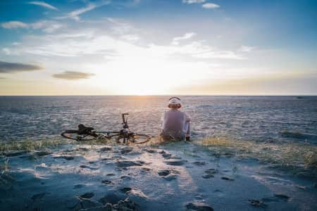 Young man sitting on the beach listen to Some music thruw his headphone and next to HIM lay his bike