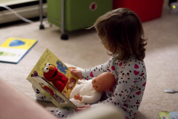 Toddler reading to her baby