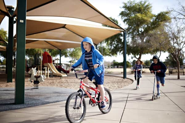 kids riding scooters and biking at the park