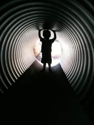 Ian playing in a tunnel