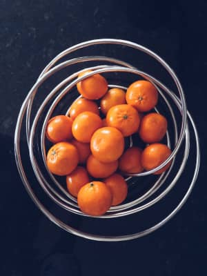 Elevated view of tangerines in wire basket
