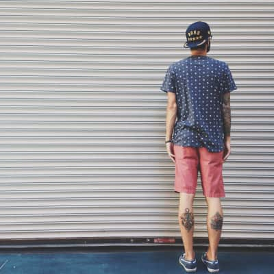 Man with tattoos standing in front of a garage door downtown.