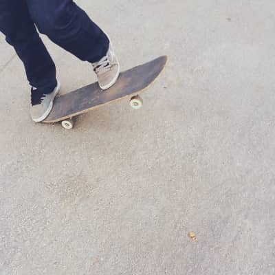 Photo from a lower perspective of someone doing a skateboarding trick.