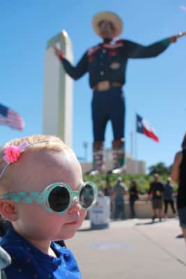 Toddler girl wearing sunglasses at the state fair of Texas with Texas flag and Big Tex in the background