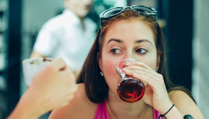 Woman drinking Turkish tea and having chat with her friend who is holding a Turkish coffee cup