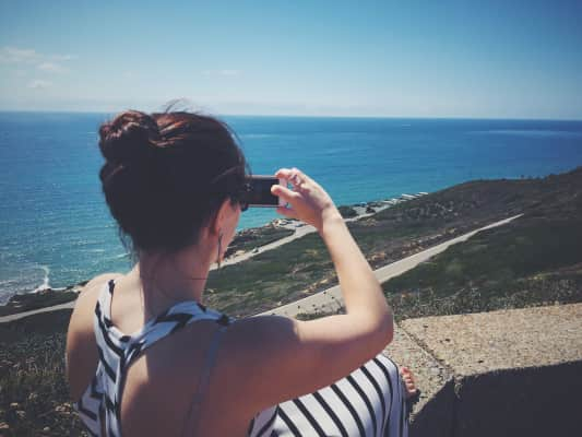 Girl taking a picture of the ocean with her iPhone