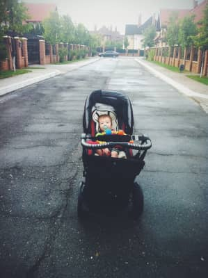 Little child in the carry on a road