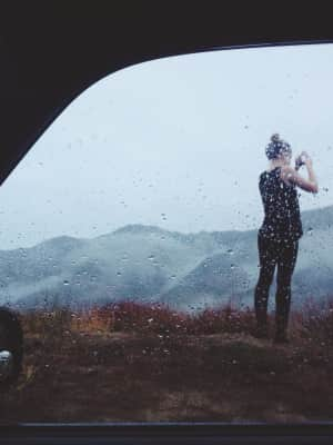 Young woman on rainy foggy mountain taking a picture with mobile phone