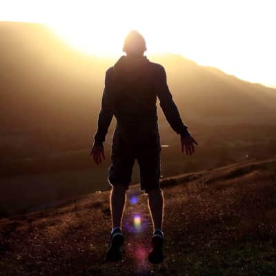 Young silhouetted man jumping into the sunlight at golden hour