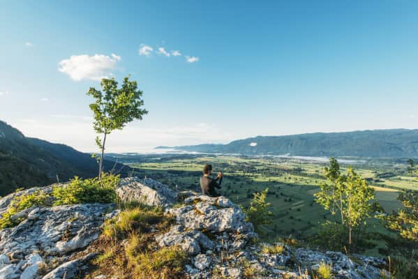 Man sitting at the top of the hill and taking photos of the picturesque valley below. Vivid colors of the meadows and fields.