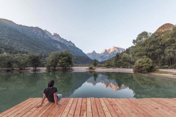 Man on the pier at the Jasna Lake in Kranjska Gora observing the amazing mountain landscape.
