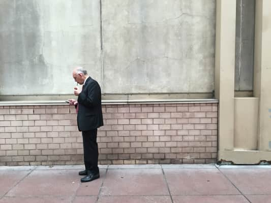 "An #👴 man smokes his pipe early this morning just outside the London Hotel. Scrawled on the wall: ""August 19"" #nyc"