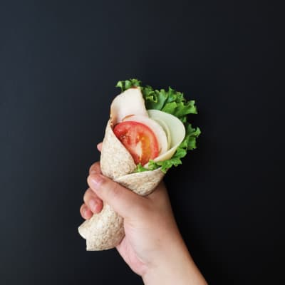 Healthy smoked turkey and provolone wrap with lettuce, tomato and onion