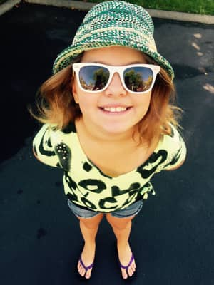 Young girl smiling big with a hat and sunglasses on.