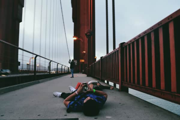 Friends laying down at the Golden Gate Bridge.
