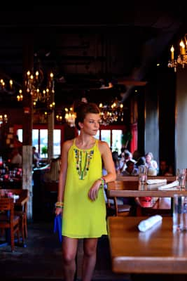 Young woman dressed up standing in a restaurant.