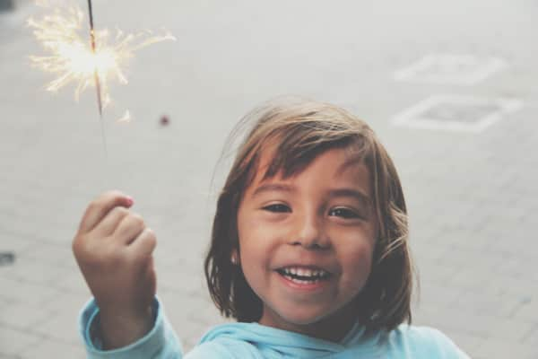 Girl with firework for holiday celebration.