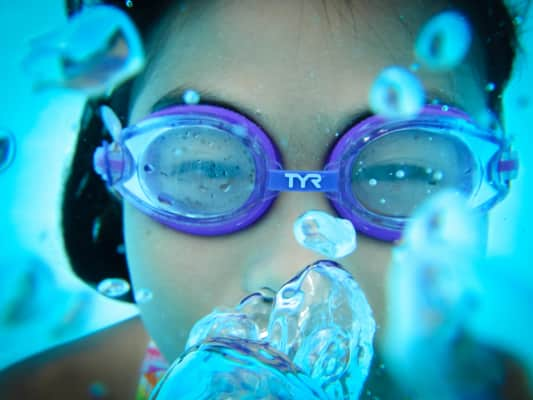 Asian girl swimming underwater exhaling air