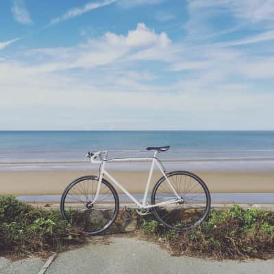 White bicycle in foreground with beach and sky in background.
