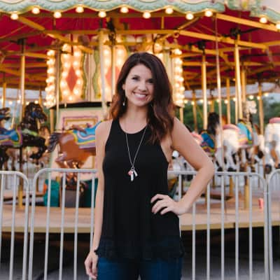Young adult woman posing in front of a carousel.