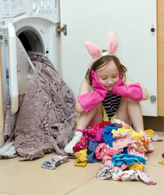 the girl sits tired on a pile of clothes with washing machine
